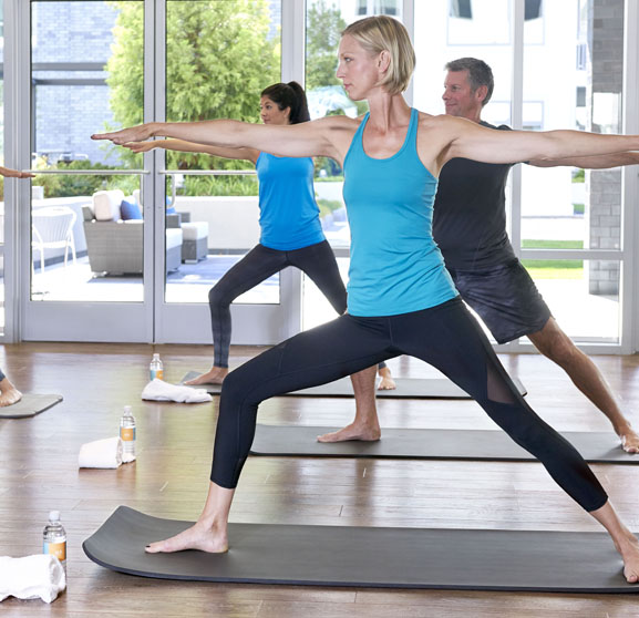 Yoga class in brightly lit studio with large windows