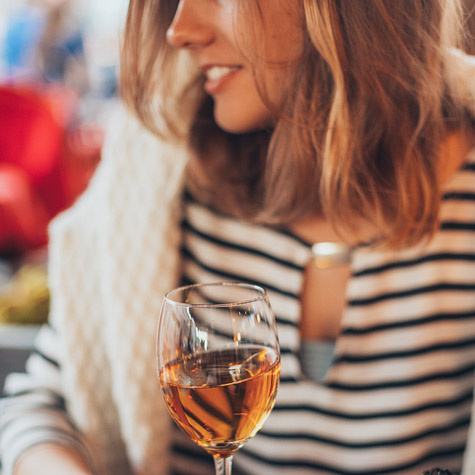 Woman in striped shirt holding a glass of rose wine