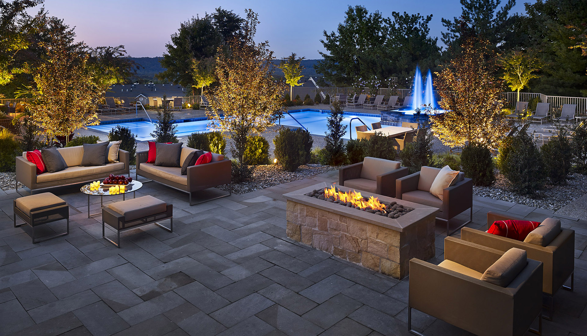 AVE Malvern's courtyard at dusk with exterior chairs, a firepit, and a pool